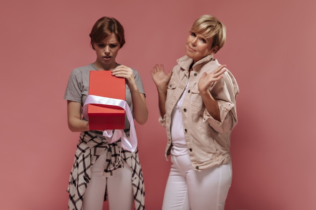 Teleurgesteld meisje met donkerbruin haar op zoek naar rode geschenkdoos en poseren met blonde dame in witte en beige kleding op roze achtergrond.