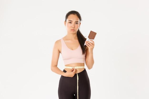 Teleurgesteld somber aziatisch meisje dat taille met meetlint meet en mokkend omdat ze geen chocoladereep kan eten terwijl ze afvallen op dieet.