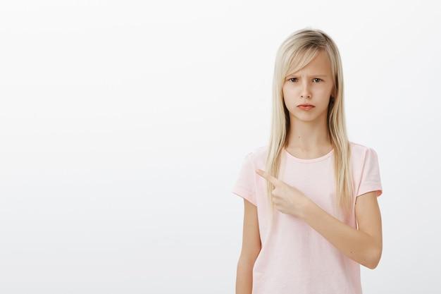 Teleurgesteld somber kind dat naar links wijst
