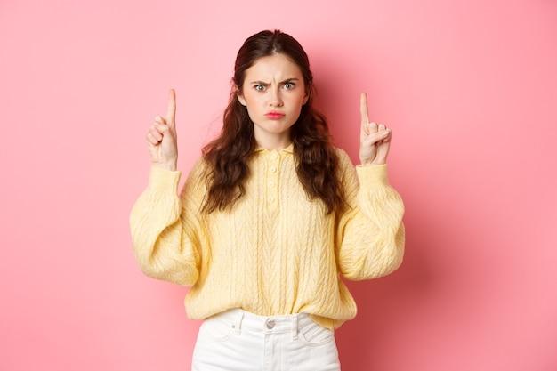 Teleurgesteld somber meisje klaagt, fronsend en wijzende vingers omhoog naar slecht bord of logo, ontevreden over iets, staande tegen roze muur.