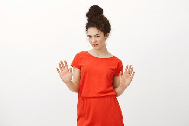 Teleurgesteld twijfelachtig aantrekkelijke vrouwelijke collega in een stijlvolle rode jurk, handpalmen opheffend in nee of stop gebaar