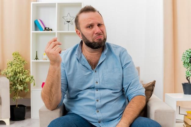 Teleurgesteld volwassen slavische man zit op fauteuil gebaren geld handteken in de woonkamer