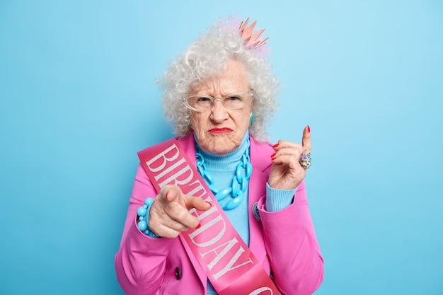 Teleurgesteld volwassen vrouw loenst gezicht wijst direct naar jou nodigt op haar verjaardagsfeestje gekleed in feestelijke kleding boos met aanstootgevende woorden over haar leeftijd draagt lichte make-up staat binnen