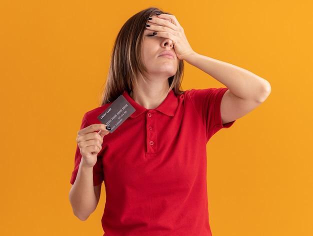 Teleurgesteld vrij kaukasisch meisje legt hand op gezicht en houdt creditcard op oranje