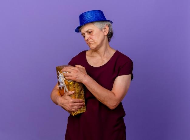 Teleurgestelde bejaarde vrouw met feestmuts houdt geschenkdoos geïsoleerd op paarse muur met kopie ruimte