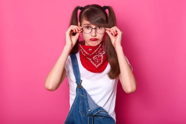 Teleurgestelde charismatische jongedame met pony en lange staartjes heeft een fronsend gezicht, raakt haar bril aan en kiest een comfortabele houding