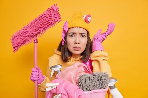 Teleurgestelde drukke huisvrouw die boos is op kinderen die rotzooi maken in huis houdt dweil vast en doet de was ziet er ontevreden uit, omdat er veel werk te doen is geïsoleerd over gele achtergrond. huishoudconcept