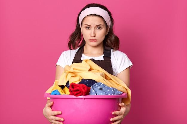 Teleurgestelde emotionele vrouw met lichte hoofdband, wit t-shirt en bruine schort, met wasgoed, uitgeput van huishoudelijke taken