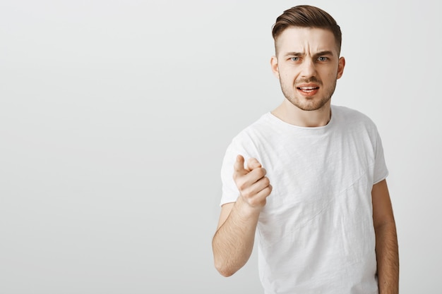 Teleurgestelde en boze jongeman wijzende vinger in beschuldiging, iemand uitschelden