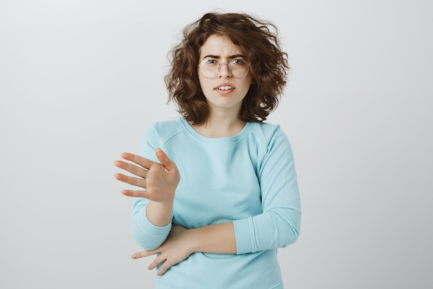Teleurgestelde en overstuur jonge vrouw hoofdschuddend in ontkenning, iets afwijzen of verbieden, nee zeggen