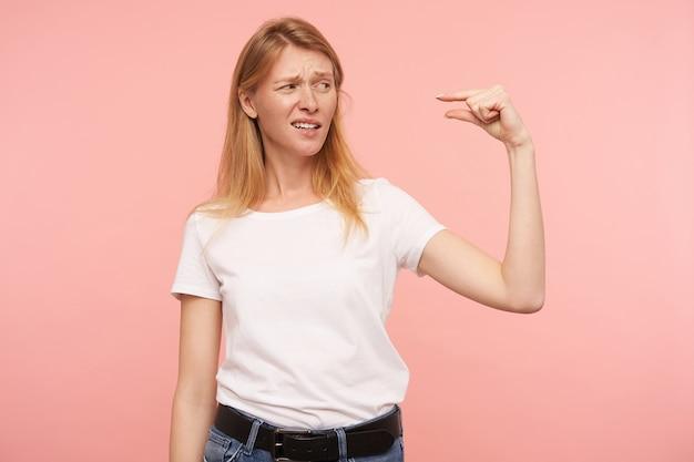 Teleurgestelde jonge aantrekkelijke langharige roodharige vrouw grimassen haar gezicht terwijl ze iets onzichtbaars meet met vingers, staande tegen roze achtergrond