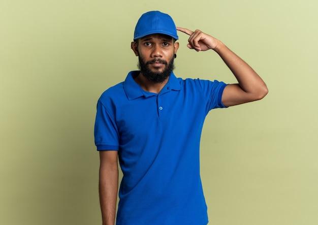 Teleurgestelde jonge afro-amerikaanse bezorger wijzend op zijn pet geïsoleerd op olijfgroene muur met kopieerruimte