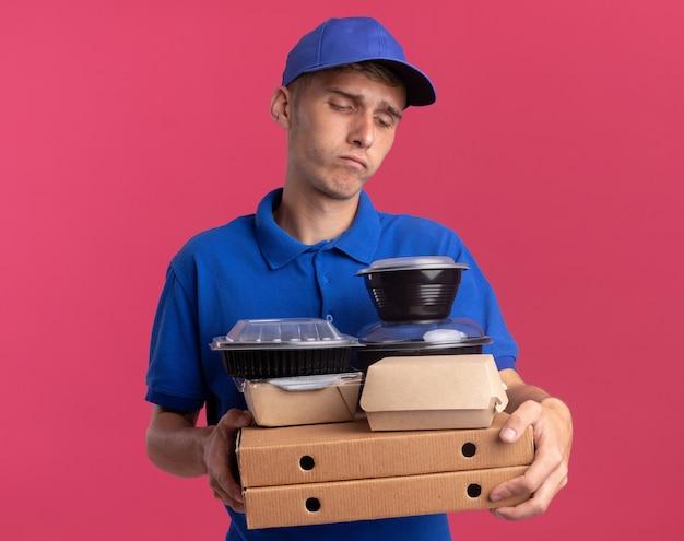 Teleurgestelde jonge blonde bezorger houdt en kijkt naar voedselcontainers en -pakketten op pizzadozen geïsoleerd op roze muur met kopieerruimte