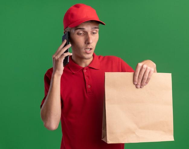 Teleurgestelde jonge blonde bezorger houdt papieren pakket vast en praat aan de telefoon
