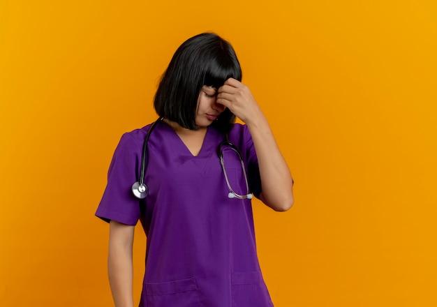 Teleurgestelde jonge brunette vrouwelijke arts in uniform met stethoscoop legt hand op voorhoofd