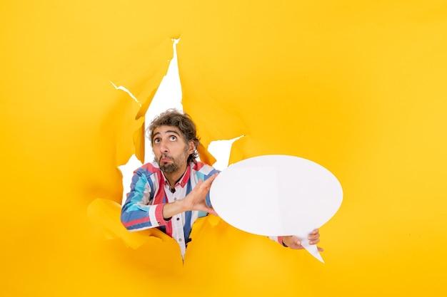 Teleurgestelde jonge kerel die een witte pagina aanwijst met vrije ruimte in een gescheurd gat in geel papier