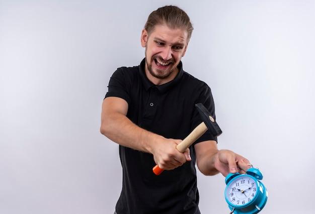 Teleurgestelde jonge knappe man in zwart poloshirt met een hamer gaat wekker in zijn hand breken met agressieve uitdrukking op gezicht staande op witte achtergrond