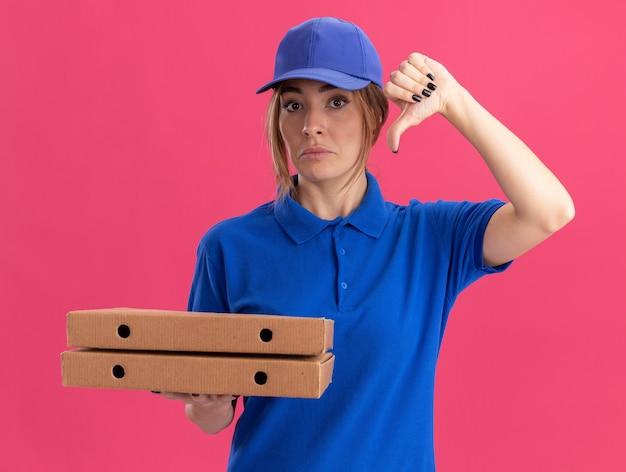 Teleurgestelde jonge mooie bezorger in uniform duimen naar beneden en houdt pizzadozen geïsoleerd op roze muur
