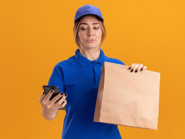 Teleurgestelde jonge mooie bezorgvrouw in uniform houdt papieren pakket en kijkt naar telefoon geïsoleerd op oranje muur