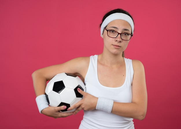 Teleurgestelde jonge sportieve vrouw in optische bril met hoofdband en polsbandjes houdt bal geïsoleerd op roze muur