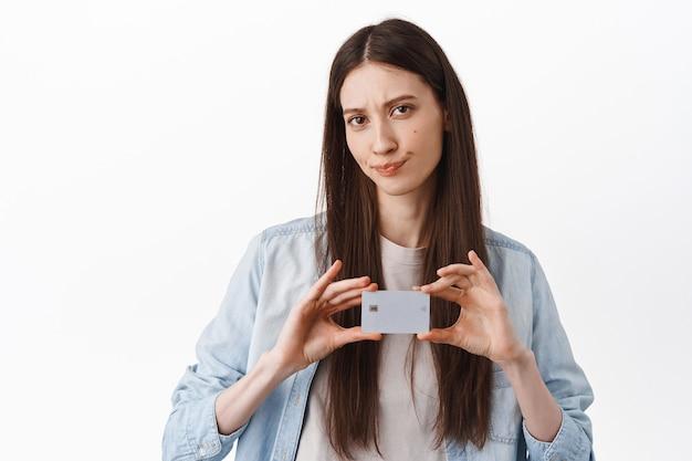 Teleurgestelde jonge vrouw die bankcreditcard toont, grijns en twijfelachtig kijkt, ontevreden fronsend, staande over witte muur