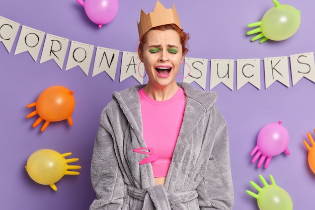 Teleurgestelde jonge vrouw draagt kroon en kamerjas drukt negatieve emoties uit, huilt binnenshuis tegen paarse muur met ballonnen die op een virus lijken, overstuur vanwege de verspreiding van het coronavirus