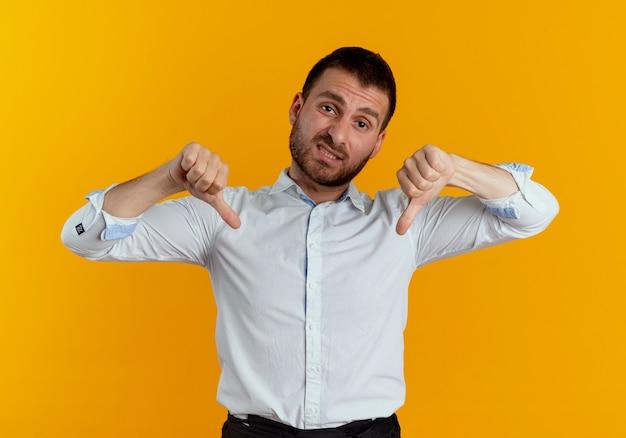 Teleurgestelde knappe man duimen naar beneden met twee handen geïsoleerd op oranje muur