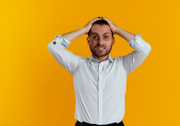 Teleurgestelde knappe man met optische bril houdt hoofd geïsoleerd op oranje muur