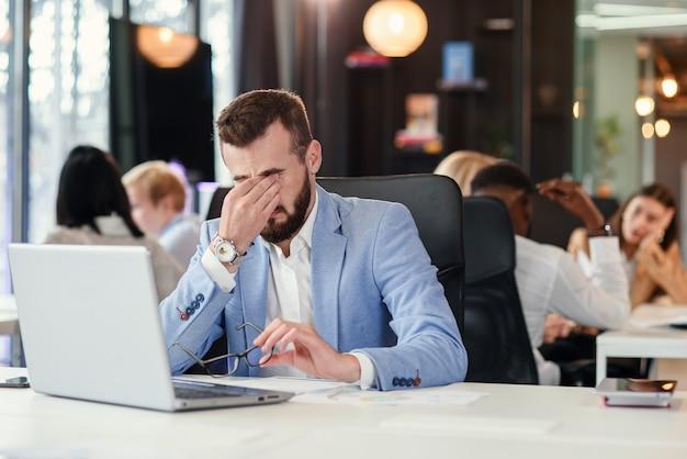 Teleurgestelde knappe zakenman kijkt uitgeput en met hoofdpijn zittend op zijn werkplek. grote fout in zaken.