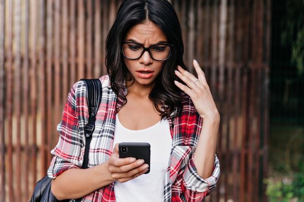 Teleurgestelde latijnse dame die in rood overhemd het smartphonescherm bekijkt. geschokt brunette vrouwelijk model rood telefoonbericht.