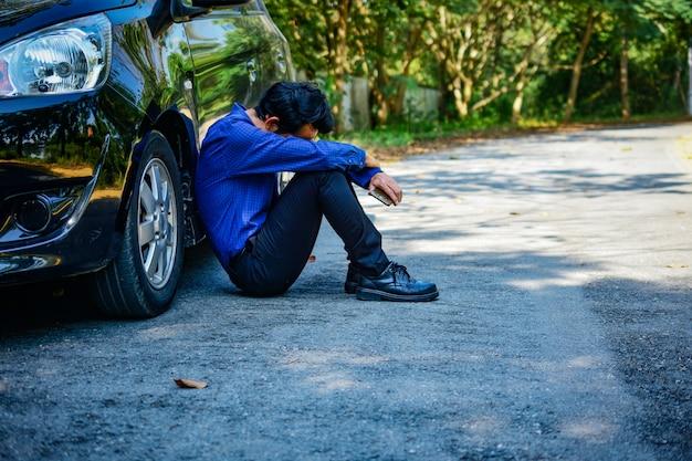 Teleurgestelde man die slimme telefoon houdt en bij auto geparkeerd op weg zit