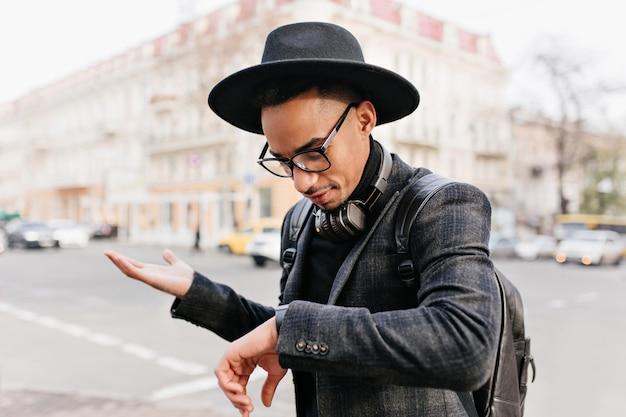 Teleurgestelde man kijkt naar polshorloge terwijl iemand wacht. bezorgd afrikaanse man in hoed staande op straat.
