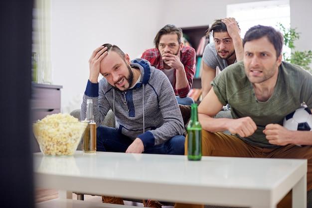 Teleurgestelde mannen kijken naar voetbalwedstrijd