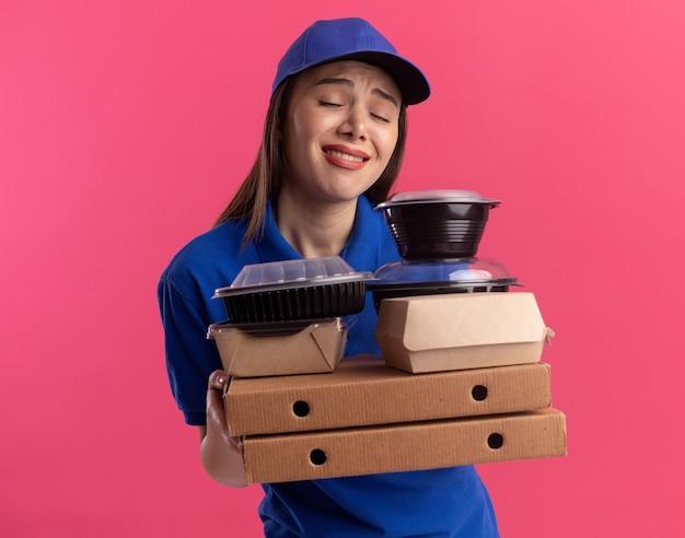 Teleurgestelde mooie bezorger in uniform houdt voedselpakket en containers op pizzadozen