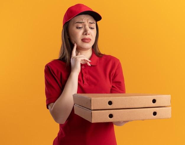 Teleurgestelde mooie bezorger in uniform legt de vinger op de kin en kijkt naar pizzadozen op oranje