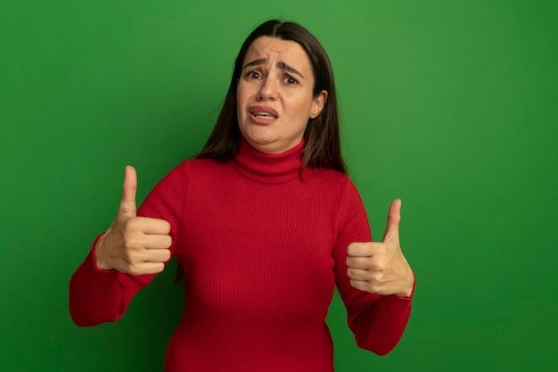 Teleurgestelde mooie vrouw thumbs up van twee handen geïsoleerd op groene muur
