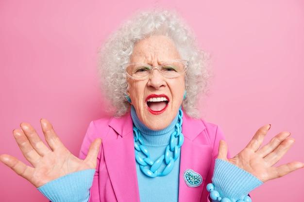 Teleurgestelde oudere krullende vrouw heft handpalmen op en roept luid negatieve emoties uit, draagt elegante kleding, rode lippenstift en make-up