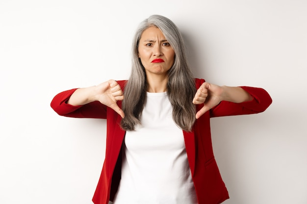Teleurgestelde oudere vrouw in rode blazer met thumbs-down, grimassen boos, afkeer en afkeuren, staande tegen een witte achtergrond.