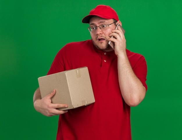 Teleurgestelde overgewicht jonge bezorger in optische glazen kartonnen doos houden en praten over telefoon geïsoleerd op groene muur met kopie ruimte