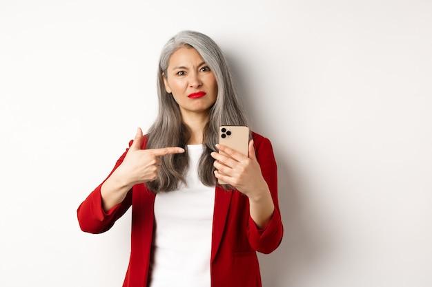 Teleurgestelde rijpe aziatische vrouw die klaagt, vinger naar smartphone richt en ontevreden kijkt, staande over witte muur.