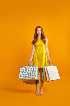 Teleurgestelde roodharige vrouw in jurk houdt winkelpakketten vast, overstuur door winkelen. mooie vrouw ziet er ongelukkig uit, houdt niet van aankopen. verveelde en vermoeide vrouw koopt cadeautjes, geïsoleerd op geel