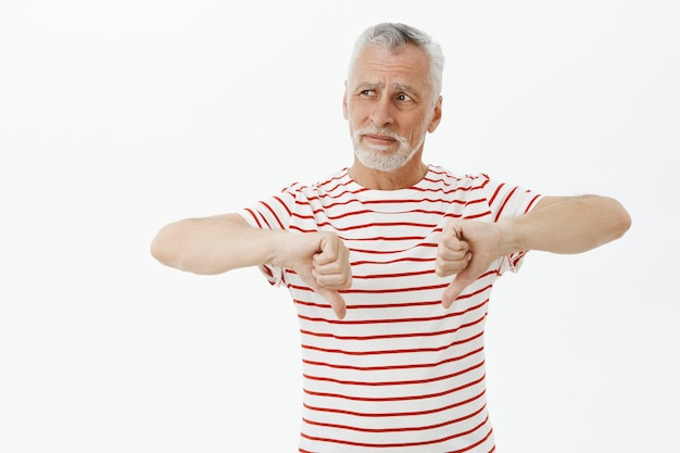 Teleurgestelde senior man in t-shirt met thumbs-down, toon afkeer gebaar