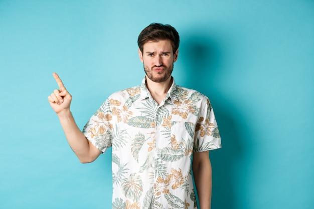 Teleurgestelde toerist krimpt ineen en fronst, wijzende vinger opzij naar lege ruimte, klaagend over slechte dingen, staande in hawaiiaans overhemd op blauwe achtergrond.