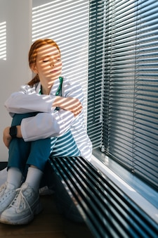 Teleurgestelde trieste jonge vrouwelijke arts in witte jas zittend op de vloer en benen bij het raam knuffelend