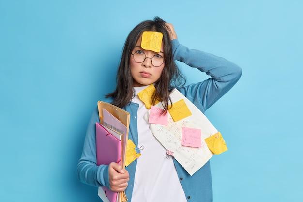 Teleurgestelde vergeetachtige jonge vrouw die moe is van het proppen voor het examen, houdt de hand op het hoofd en ziet er gestrest uit.