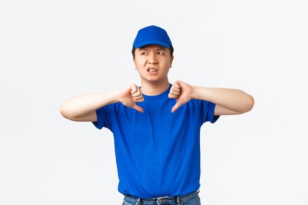 Teleurgestelde veroordelende aziatische mannelijke koerier laat negatieve feedback achter over vorig bedrijf. bezorger die er gehinderd en ontevreden uitziet, met duimen naar beneden, staande witte achtergrond.