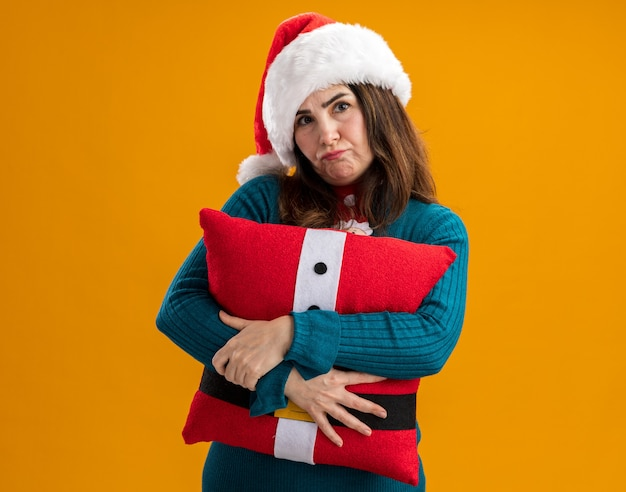 Teleurgestelde volwassen blanke vrouw met kerstmuts en stropdas van de kerstman knuffels versierd kussen geïsoleerd op een oranje achtergrond met kopie ruimte