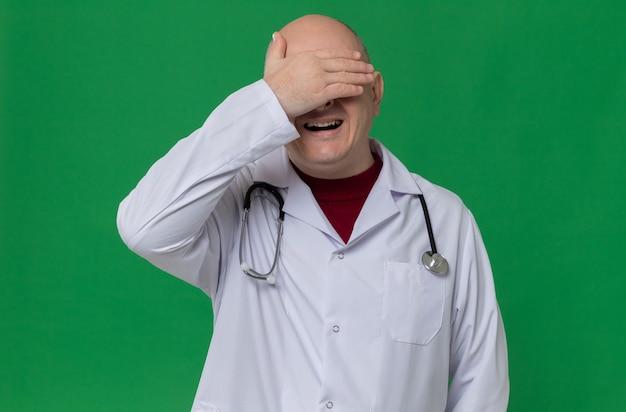 Teleurgestelde volwassen slavische man in doktersuniform met stethoscoop die hand op zijn voorhoofd legt