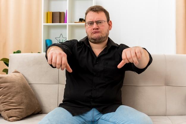 Teleurgestelde volwassen slavische man in optische bril zit op fauteuil duimen naar beneden met twee handen in de woonkamer