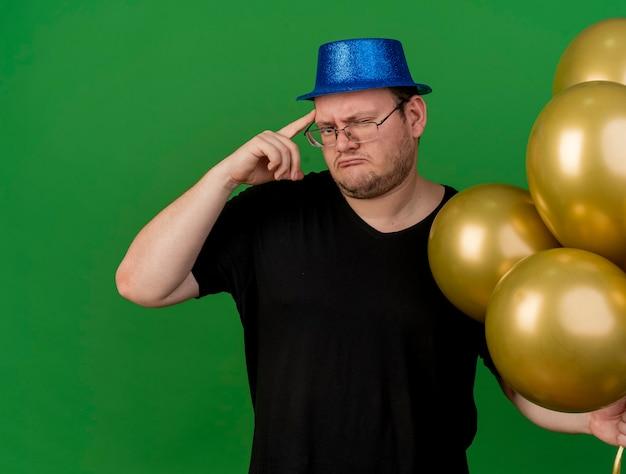 Teleurgestelde volwassen slavische man met een optische bril met een blauwe feesthoed houdt heliumballonnen vast en legt de vinger op de tempel